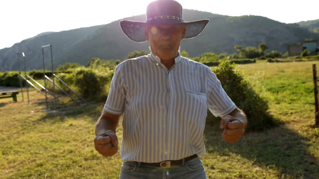 Funny senior man imitates a cowboy