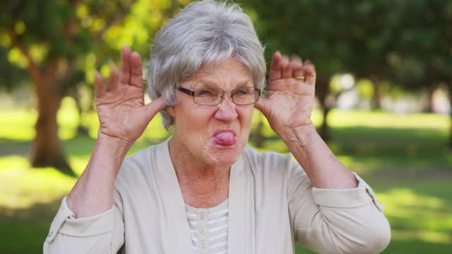 funny senior woman making faces at camera - grey hair stock videos and b-roll footage