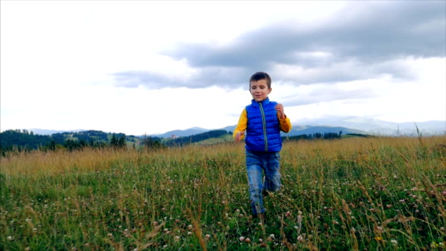 funny small boy jumping during walk in mountain - boys stock videos & royalty-free footage