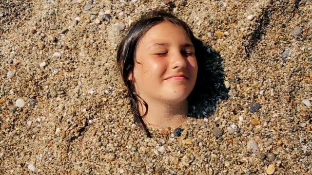 Funny teenage girl in sand on the beach