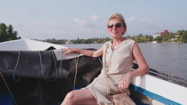 funny tropical vacations. mature 55-years-old caucasian white woman riding a motorboat. - thin stock videos & royalty-free footage