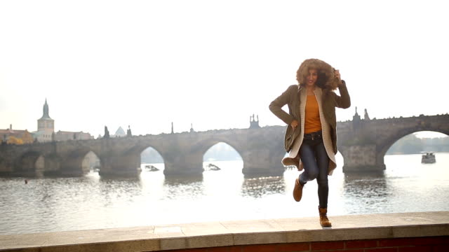 Funny woman jumping around near Charles bridge
