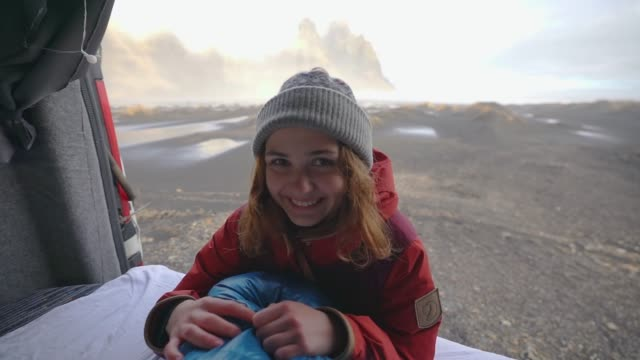Funny woman on the background of Vestrahorn mountains from camper van