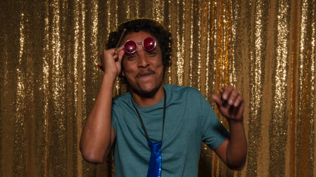 funny young man posing for photos in the photo booth at a party - sunglasses stock videos & royalty-free footage
