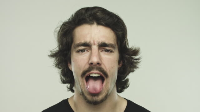 funny young man sticking out his tongue - grimacing stock videos & royalty-free footage