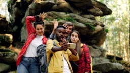 Funny young people happy friends are taking selfie in wood with mossy rocks in background, African American guy is holding smartphone, men and women are posing.