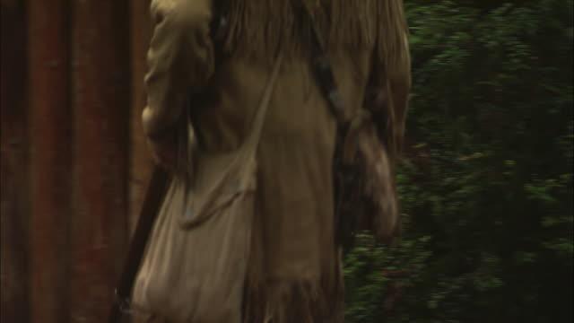 A fur trapper enters through a log gate.