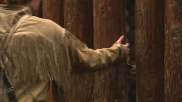 A fur trapper opens a wooden door.