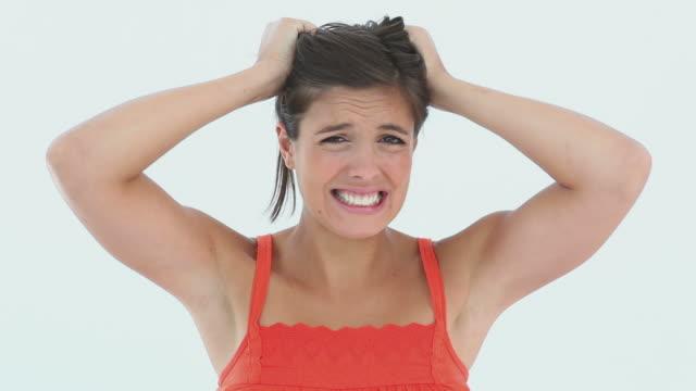stockvideo's en b-roll-footage met frustrated girl pulling her hair - tanden op elkaar klemmen