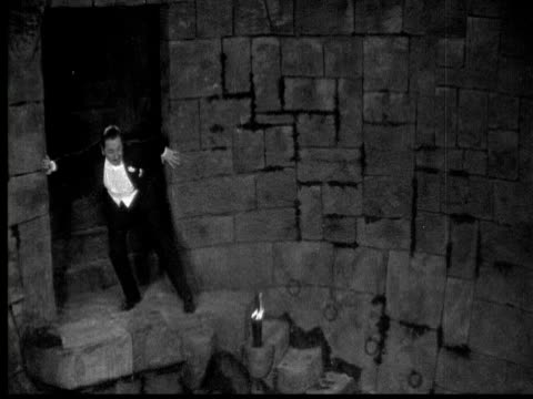 1925 ms b/w furious man ascending steps in dungeon, doors closing - dungeon stock videos & royalty-free footage