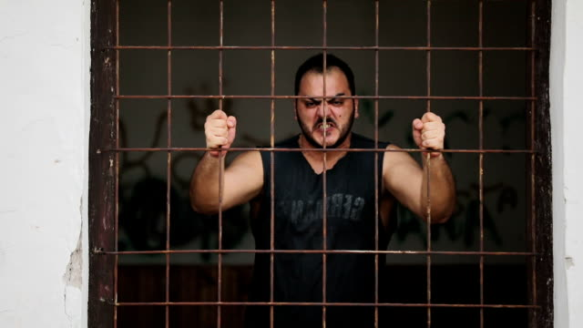 Wütender Mann hinter Gittern