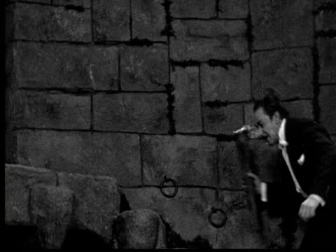 1925 ms b/w furious man with burning torch ascending steps in dungeon - 1925年点の映像素材/bロール