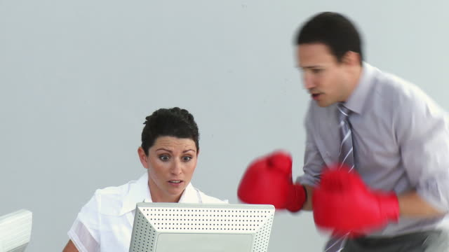 ms furious manager wearing boxing gloves talking to woman working on computer / cape town, western cape, south africa - hemd und krawatte stock-videos und b-roll-filmmaterial