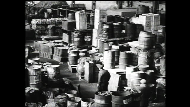 vídeos de stock e filmes b-roll de furnaces burning tended by workers inside a factory; moulds being poured and skimmed; piles of bullet shells/castings being produced; panning view of... - 1940 1949