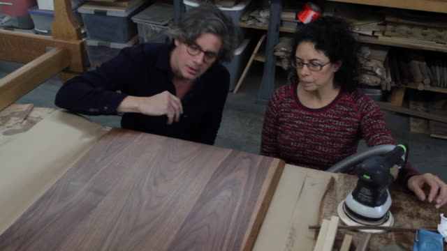 furniture designers inspect the grain in a piece of wood. - wood grain stock videos & royalty-free footage