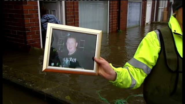 Further heavy rain and flood warnings ENGLAND South Yorkshire Bentley EXT Linda Clarke helped into her flooded home to search of her son's ashes...