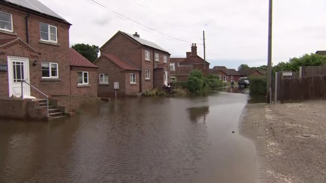 further heavy rain could exacerbate flooded areas in lincolnshire england lincolnshire wainfleet ext flooded road flood water by houses sandbags by... - lincolnshire stock videos & royalty-free footage