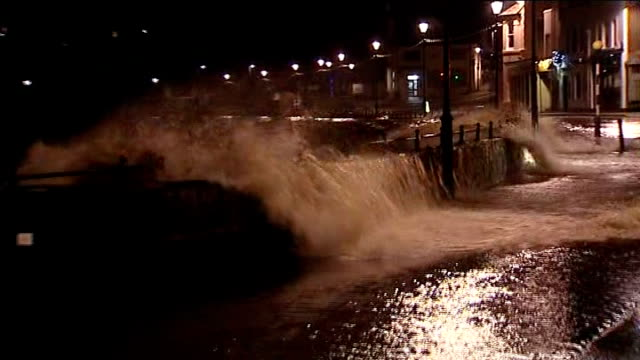 further storms and flooding hit uk; england: cornwall: bude: ext / night waves breaking over sea wall and onto promenade road onlookers stand in... - in front of点の映像素材/bロール