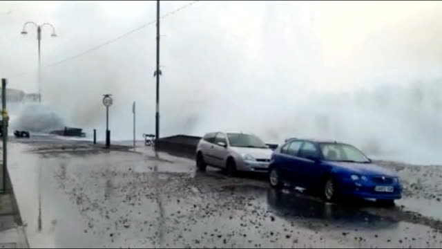 vídeos de stock, filmes e b-roll de further storms and flooding hit uk wales aberystwyth large waves breaks over seafront promenade road and parked cars as people stand taking... - aberystwyth
