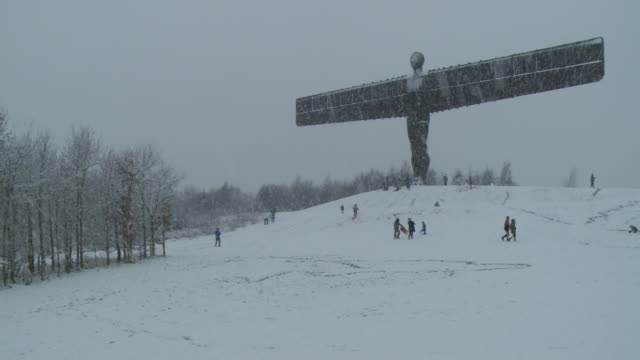 further winter storms cause travel disruption tyne and wear gateshead angel of the north statue in snow various shots of children and adults playing... - angel of the north stock videos and b-roll footage
