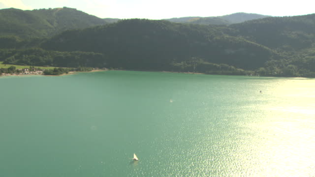Fuschlsee w/ green/blue water sailboats sunlight reflecting on surface hills amp mountains w/ green trees BG Rural resort