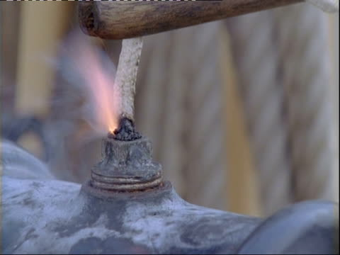 fuse of cannon being lit on board replica of hms endeavour. - cannon stock videos & royalty-free footage