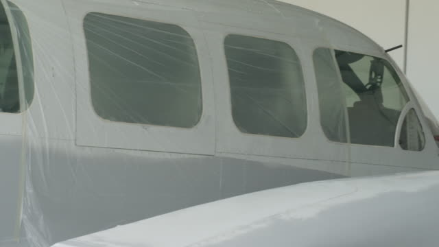PAN LS fuselage of aircraft, camera pans to mechanic sanding engine nacelle in preparation for painting