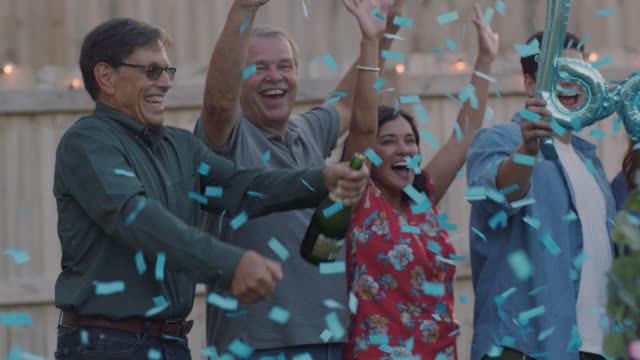 slo mo. future grandfather opens champagne as blue confetti bomb reveals it's a boy - baby boys stock videos & royalty-free footage