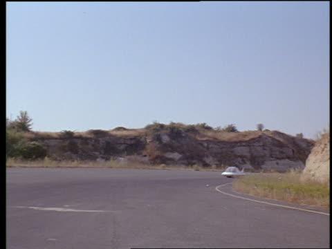 futuristic car driving along road in countryside - anno 1965 video stock e b–roll
