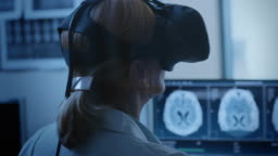 Futuristic Concept: In Medical Control Room Female Doctor Wearing Virtual Reality Headset Monitors Patient Undergoing MRI or CT Scan Procedure. Computer Displays Shows Brain Scans.