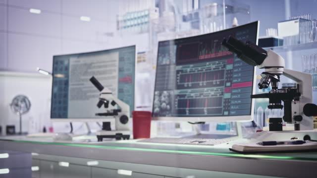 attrezzature da laboratorio futuristiche. ricerca sulle cellule del sangue sugli schermi dei computer - farmaco video stock e b–roll