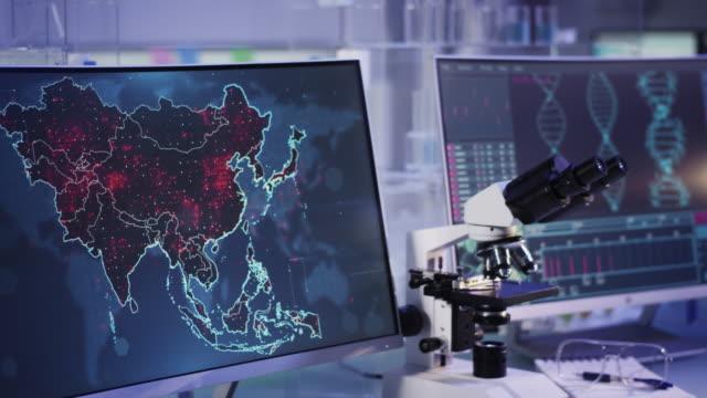 vídeos de stock e filmes b-roll de futuristic laboratory. virus spreading level on asia map. scanning dna mutations - mutação genética