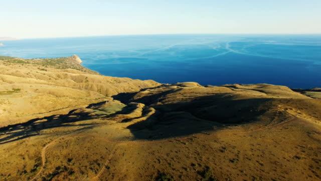 AERIAL: Futuristic landscape of desert mountains and blue sea