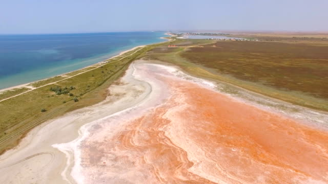 AERIAL: Futuristic landscape of red salt lake near blue sea