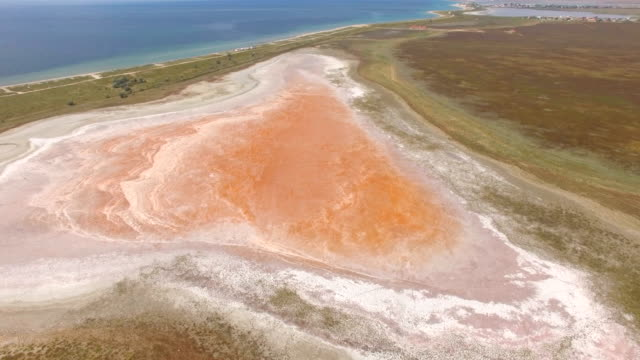 aerial: futuristic landscape of red salt lake near blue sea - multicopter stock videos & royalty-free footage