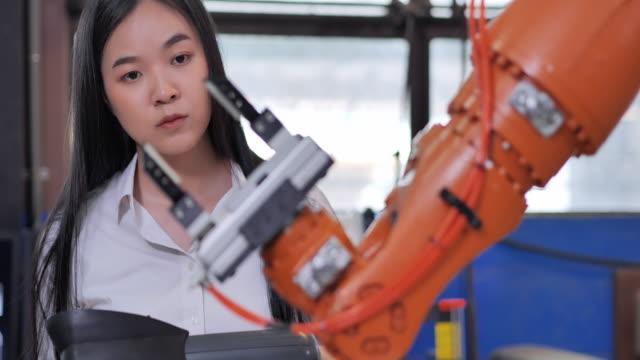 vídeos y material grabado en eventos de stock de un brazo robot protésico futurista por una adolescente ingeniera de desarrollo asiático en un laboratorio de investigación en el día. el brazo mueve sus dedos. tecnología, trabajo tardío, ciencia, liderazgo, temas de educación.industria 4.0,innovaci - robótica