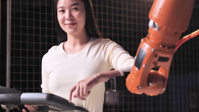 a futuristic prosthetic robot arm by a asian teenage girl smiing development engineer in a research laboratory at night of working late.arm moves its fingers.technology,working late,science,leadership,education topics.industry 4.0,innovation,women in stem - programmer stock videos & royalty-free footage