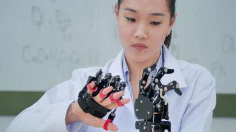 a futuristic prosthetic robot arm by a teenage girl development engineer in a research laboratory at day of working late.arm moves its fingers.education,technology,teamwork,working late,innovation,science and people concept.education topics.industry 4.0 - engineering stock videos & royalty-free footage
