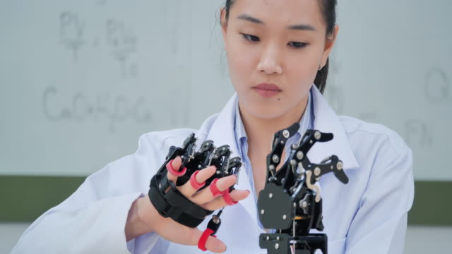 a futuristic prosthetic robot arm by a teenage girl development engineer in a research laboratory at day of working late.arm moves its fingers.education,technology,teamwork,working late,innovation,science and people concept.education topics.industry 4.0 - evoluzione video stock e b–roll