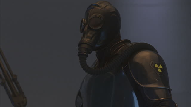 A futuristic soldier in a radiation suit and gas mask warding off an attacker.