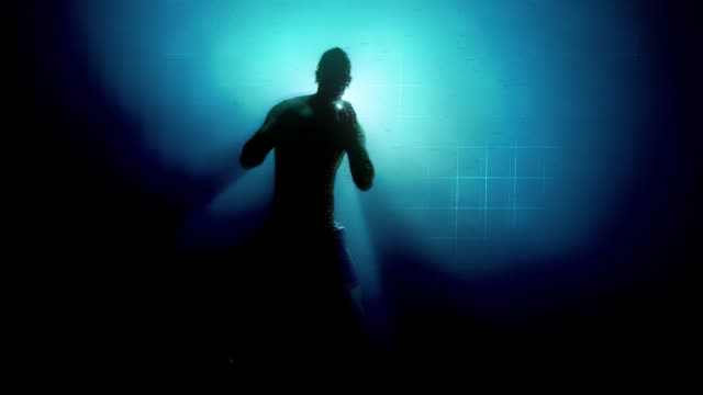 futuristic style slow motion of silhouette of man doing boxing guard move with light behind him. caucasian male. - kickboxing stock videos & royalty-free footage