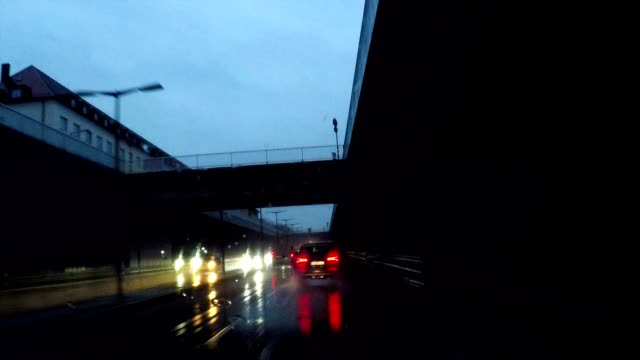 futuristic vision of driving at night in the rain along a modern traffic corridor, munich, germany - high point video stock e b–roll