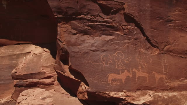 fying around ancient petroglyphs 4k, Drone aerial view of Ancient petroglyphs anthropomorphic native american and paleolithic petroglyphs. Including horses, jesus, crosses, staff, alien and human carvings. Located on the Utah and Arizona border
