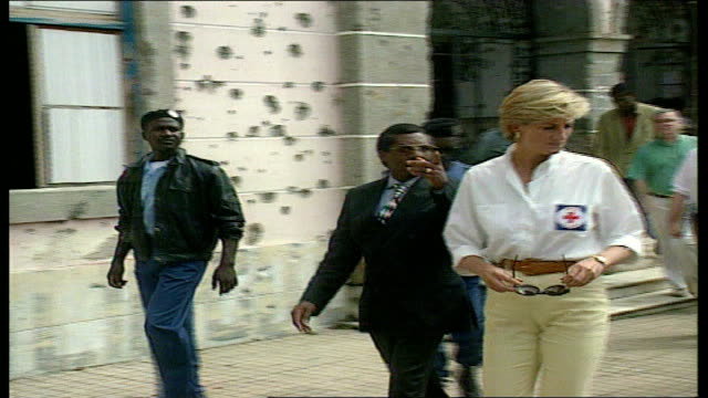 1815 1930 g1815 LIB Angola Diana in slacks Red Cross shirt along past bulletmarked building CMS Diana examining munitions