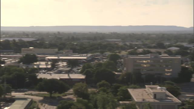 gaborone city w/ low & mid-rise buildings, trees, traffic on streets below. - ボツワナ点の映像素材/bロール