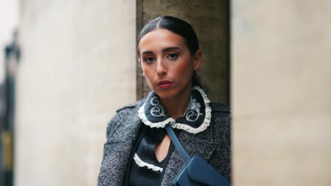 gabriella berdugo wears a gray long wool coat, a blue dior small bag, a black dress with white ruffled collar and floral embroidery, blue pointy high... - human leg stock videos & royalty-free footage