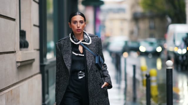 vídeos de stock e filmes b-roll de gabriella berdugo wears a gray long wool coat, a blue dior small bag, a black dress with white ruffled collar and floral embroidery, blue pointy high... - vestido preto