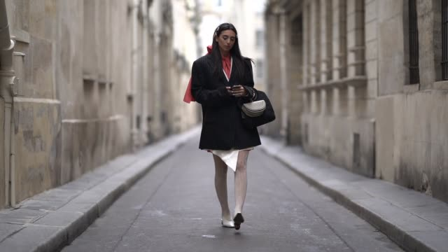 stockvideo's en b-roll-footage met gabriella berdugo wears a striped blazer jacket an orange scarf a chloe bag gucci tights white shoes outside thom browne during paris fashion week... - panty