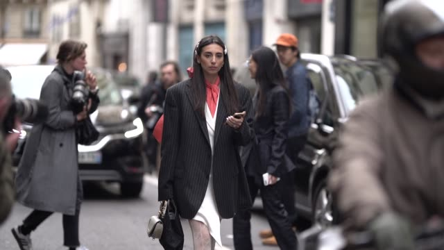 gabriella berdugo wears a striped blazer jacket an orange scarf a chloe bag gucci tights white shoes outside thom browne during paris fashion week... - collant video stock e b–roll