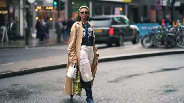 gabriella berdugo wears sunglasses, a beige trench coat, white pants, a necklace, earrings, a white bag, blue boots, during london fashion week... - トレンチコート点の映像素材/bロール